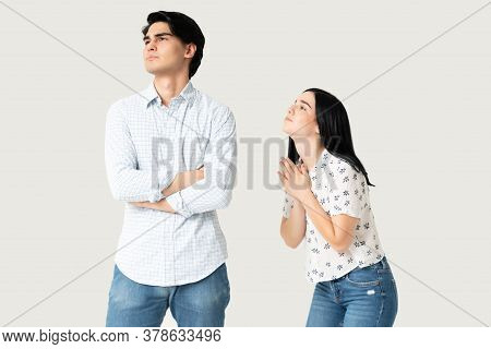 Young Woman Apologizing Angry Hispanic Man With Hands Clasped