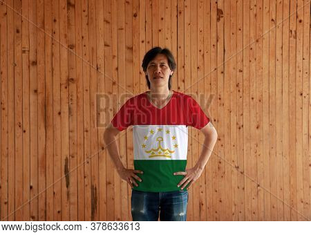 Man Wearing Tajikistan Flag Color Shirt And Standing With Akimbo On The Wooden Wall Background, Red