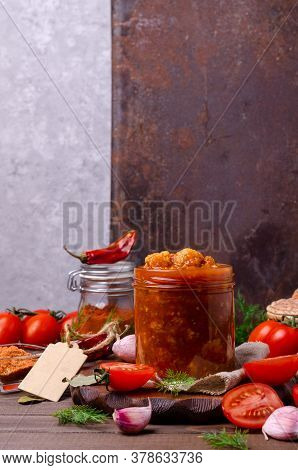 Canned Cauliflower With Vegetables In Tomato Sauce In A Jar On A Dark Wooden Background. Selective F