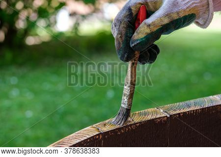 A Man (painter) Paints The Ends Of A Wooden Tabletop With Varnish, In The Background You Can See A G
