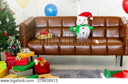 Snowman On The Sofa With A Gift Box And Christmas Tree