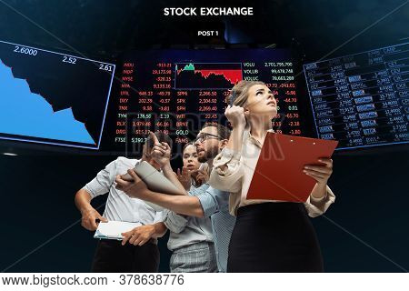 Intense. Nervous Tensioned Investors Analyzing Crisis Stock Market With Charts Of Falling Stock Exch