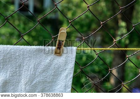 A White Towel Hangs On A Yellow Clothesline, Fastened With A Plastic Clothespin, But Against A Rusty