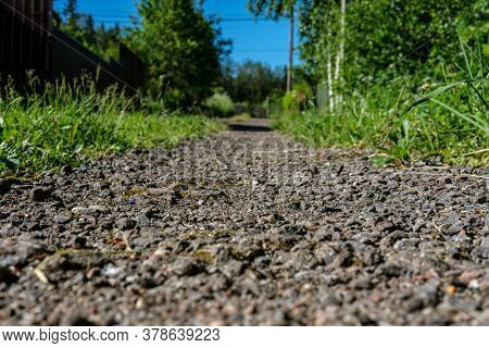 A Path Made Of Small Stones And Old Asphalt, Extending Into The Distance And Leading To The Garden,