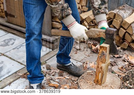 A Man Chopping Birch Firewood (logs) With A Metal Ax With A Wooden Handle. Logging Firewood For The