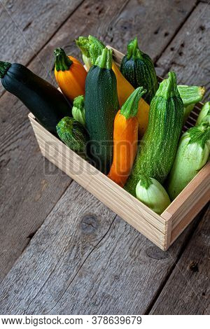 Set Of Multi-colored Zucchini In A Wooden Box. Vegetable Squash On A Wooden Background. A Table With