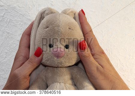 A Furry Hare In A Woman's Arms. Toy Rabbit.