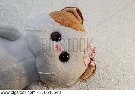 Portrait Of A White Toy Cat On A White Background.