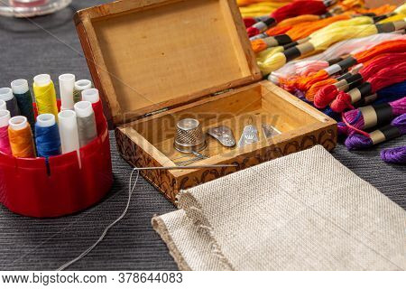 The Sewing Accessories Are In A Wooden Box. The Mulina And Colored Threads Lie On The Table Next To