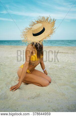 Vertical Shot Sexy Bikini Tanned Body Woman Wearing Big Straw Hat Sitting On Sand Beach By Blue Sea.