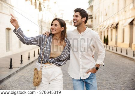 Image of young caucasian brunette couple smiling and pointing fingers aside while walking on city street