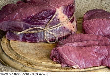 Pieces Of Raw Beef Meat On Cutting Board. Beef Tenderloin, Sliced In Portions And Large Piece Of Rum