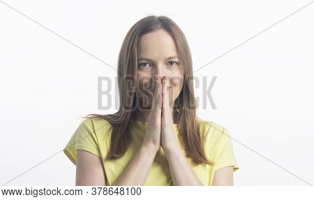 Young Caucasian Woman With Light Smile, Closing Her Mouth With Palms Holding Together Looking At Cam