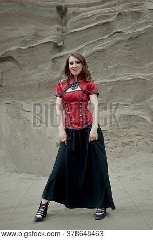 Beautiful Anime Woman In The Sand. Red Corset On The Girl's Body. Bright Red Makeup On The Face
