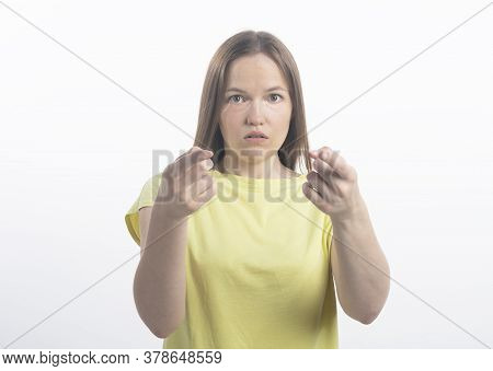 Surprised European Woman Pointing At Camera With Both Index Fingers Standing Over White Background.