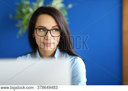 A Young Woman With Glasses Sits In The Office In Front Of The Monitor. Beautiful Female Worker With