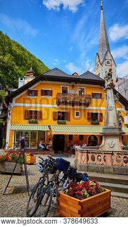 Hallstatt, Austria. Scenic postcard view of historic village town square with statue and church tower. Traditional colorful houses at Hallstatter See in Austrian Alps. Salzkammergut region.