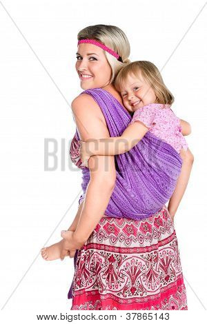 Happy Mother Carrying A Baby Girl On Her Back In Sling Isolated On White Background
