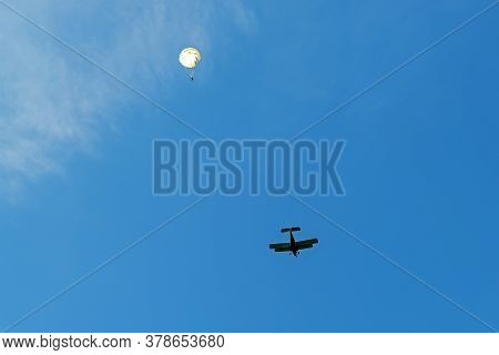 The Landing Of The Parachutist On The Parachute The Canopy Of The Plane Of A Biplane Against The Blu