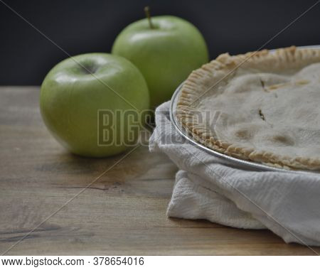 An Apple Pie Wrapped In White Dishcloth On Wooden Table, Viewed From The Side, Decorated With Two Gr