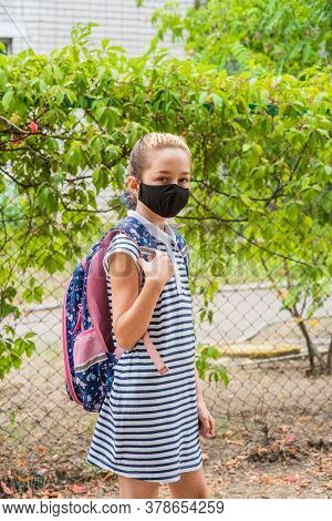 Schoolgirl Girl In A Black Protective Mask With A Backpack. Schoolgirl In A School Uniform. Fall. Ba