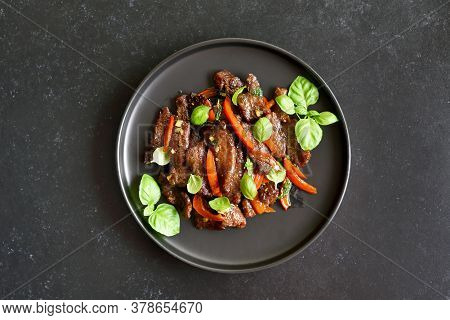 Thai Style Stir-fry Beef With Vegetables On Plate Over Dark Stone Background. Top View, Flat Lay