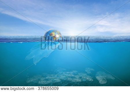 Creative Background, World Wrapped In Plastic Floating In The Ocean, A Bottle In The Water. The Conc