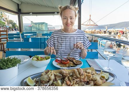 Beautiful Female Tourist Eating Delicious Sea Food On Summer Vacation In Traditional Croatian Costal