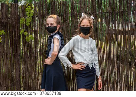 Two Schoolgirls Wearing Masks And Going Back To School During Covid-19 Pandemic.two Schoolgirls Wear