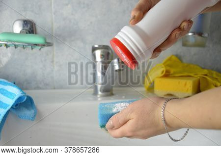 Girl Pours Cleaning Agent Onto A Sponge To Wash The Bathroom Sink. Detail Of Woman Hands Washinga A