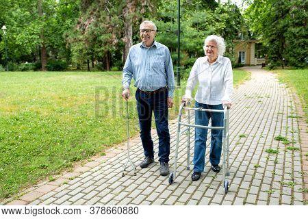 Senior Man Using A Walking Cane Accompanied By A Senior Lady Strolling With Folding Walker