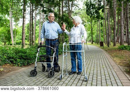 Elderly Couple Holding On To Walking Helper With One Hand