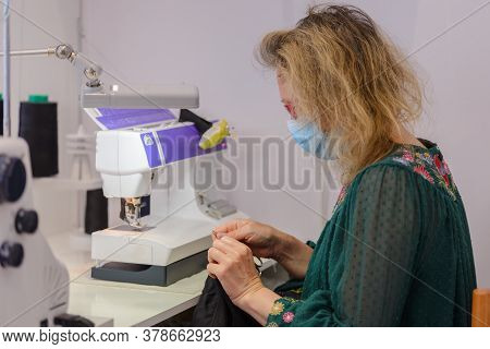 Woman Tailor With A Medical Mask On Her Face Works In A Sewing Atelier, Work During Quarantine, Covi
