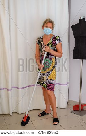 Young Woman With A Medical Mask On Her Face Sweeping The Floor In A Sewing Atelier