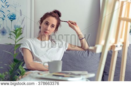 Artist Girl Sits Home Sofa, Looks Malbert, Examines Painting, Holding Paintbrush, Background Table W