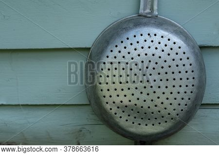 Close-up: A Metal (aluminum) Slightly Dented Colander With Many Small Holes Hanging On A Wooden Wall
