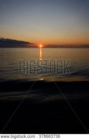 A Beautiful Sunset In Twilight Sky Over The Lake, The Sun Sets Over The Horizon, The Sun Path Is Ref