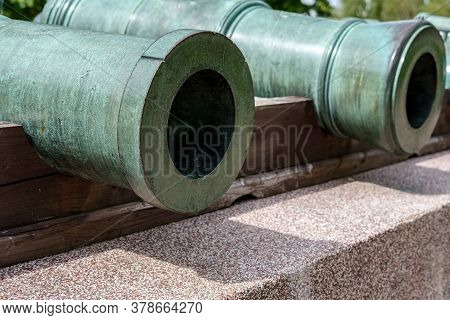 Close-up Of Old Green Bronze Cannons, Lying On A Pedestal Of Concrete And Granite.