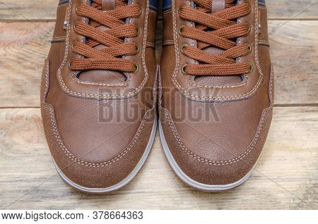 Men's Sports Brown Shoes With Blue Inserts On A Wooden Background, Sock Part Of Men's Shoes, View To