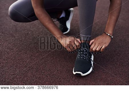 Black Girl Laces Up Her Sneakers While Doing Sports On The Street. Outdoor Fitness Concept.