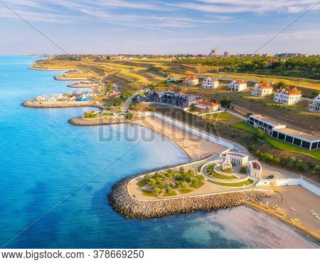 Aerial View Of Beautiful Sandy Beach, Blue Sea, Promenade, Houses, Transparent Water, Green Trees On