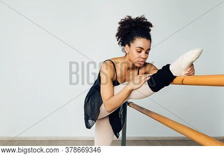 Female Ballet Dancer Stretching Her Leg. Young Woman Preparing For A Ballet Class In A Studio.