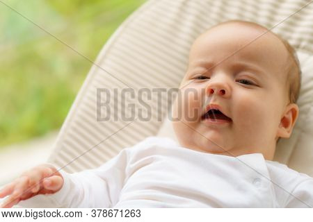 Cute Innocent Little Newborn Awake In A Hammock. The Child Looks Around. Mode For Newborn Time Outdo