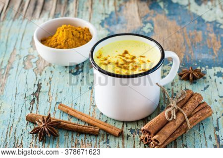 Detox Drink. Golden Milk With Turmeric And Cinnamon In A Metallic White Mug On An Old Wooden Table.