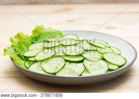 Traditional Salad Of Slices Of Cucumber And Sesame Seeds On A Plate On A Wooden Table. Vegetarian Fo
