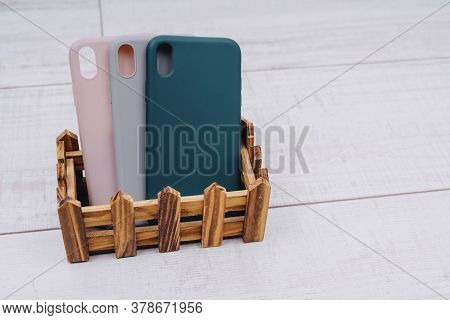 Three Silicone Cases For A Smartphone Stand In A Wooden Stand. Grey, Green And Pink Smartphone Cases