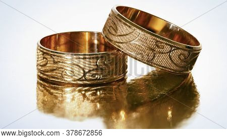 Two Gold Wedding Rings With A Thread On A White Background.