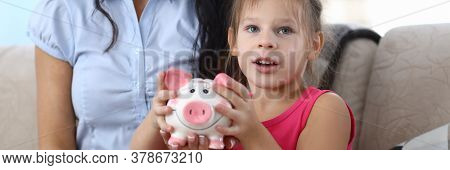 Portrait Of Attractive Little Kid With Pink Piggy Bank. Smiling Mother Looking At Camera With Gladne