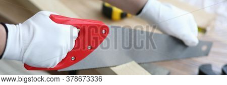 Close-up Of Worker Hands Using Special Carpentry Tool For Sawing Wooden Timber. Woodworker In Protec