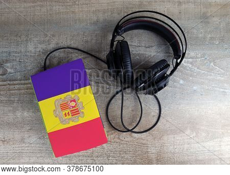 Headphones And Book. The Book Has A Cover In The Form Of Andorra Flag. Concept Audiobooks. Learning